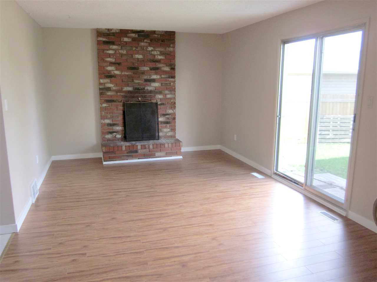 Large family room with wood burning fireplace and laminate flooring.