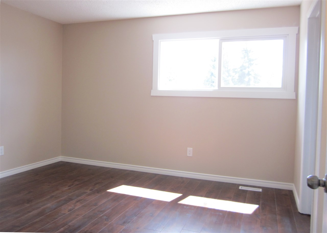 Large master bedroom with laminate flooring.