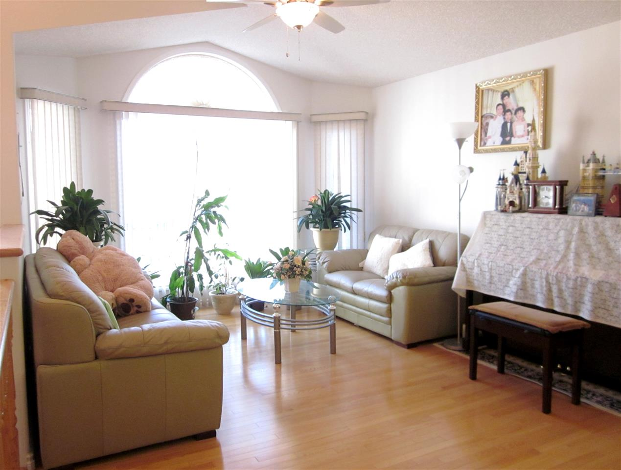 Bright living room with bay window and gleaming hardwood flooring.