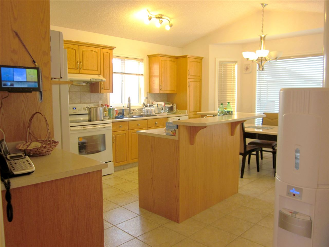Beautiful kitchen has island with raised eating bar, corner pantry, tiled backsplash, and breakfast nook with bay window.