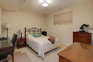 One of two large lower level bedrooms both featuring large walk-in closets with organizers and large windows.