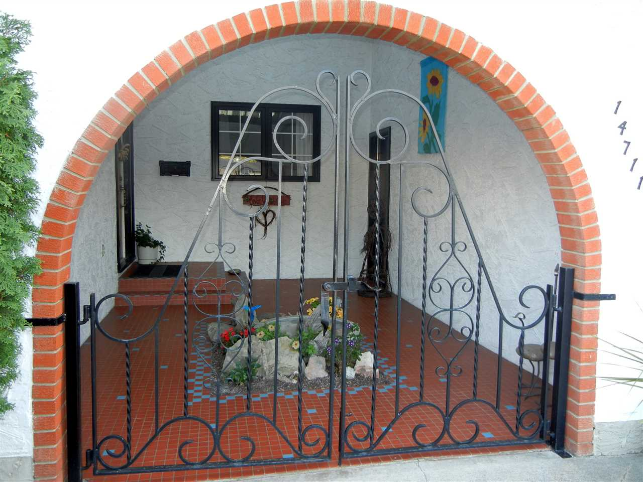 Covered entrance with wrought iron gate and skylight.