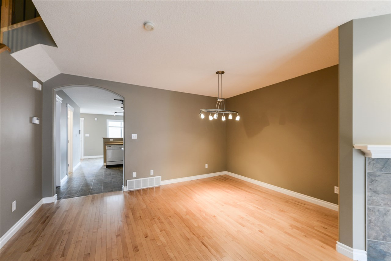 Spacious area and partially separated by gas fireplace. Hardwood flooring.