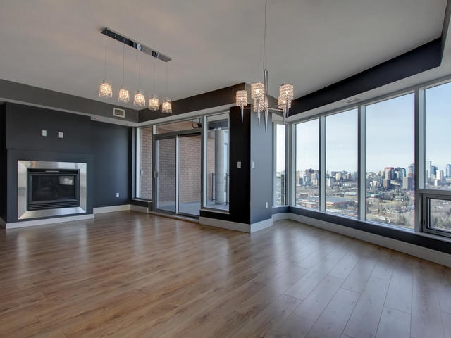 Features gas fireplace and access to balcony with views of river and downtown.