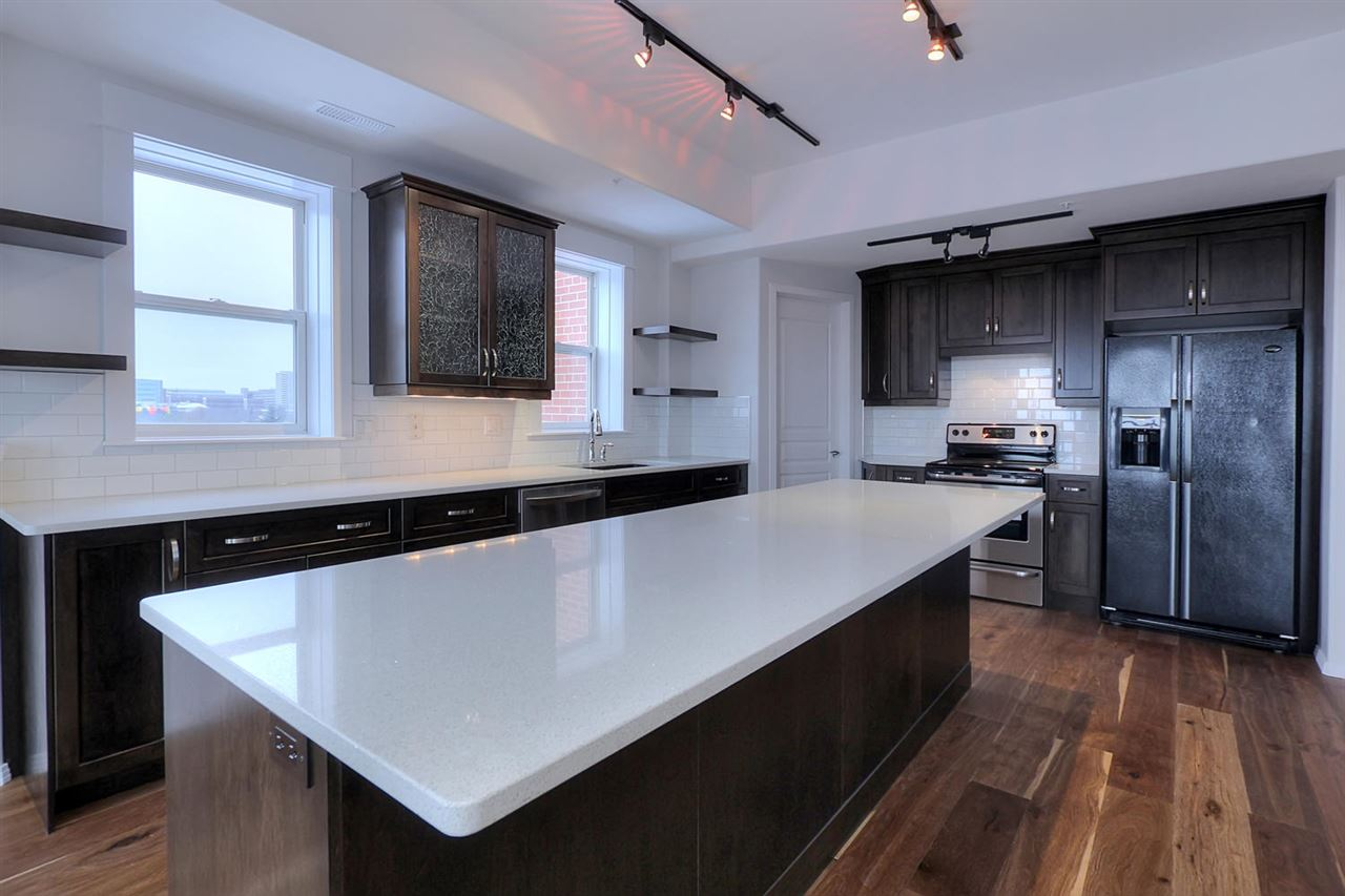 The stunning chefs kitchen features loads of custom made espresso colored maple cabinets, lots of countertop space, massive island (10 ft wide) with eating bar, quartz countertops, porcelain subway tile backsplash, granite sink & newer appliances.