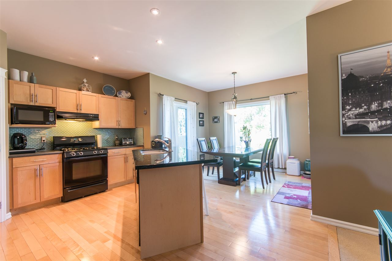 The kitchen features ample cabinets and a large centre island with granite counter top.