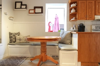 dinette has bench seating which holds extra storage.