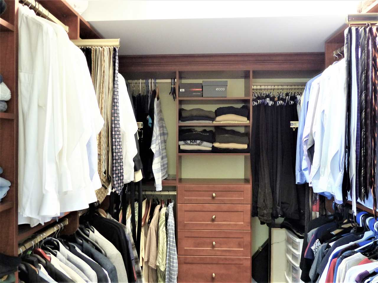 This custom built walk-in closet is wonderful for keeping you organized. Contains tie racks, belt racks, shoe shelving and drawers.
