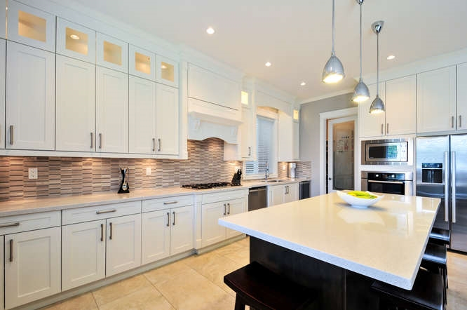 Oversized island features soft close cabinetry, large pull out drawers, gorgeous pendulum lighting.
