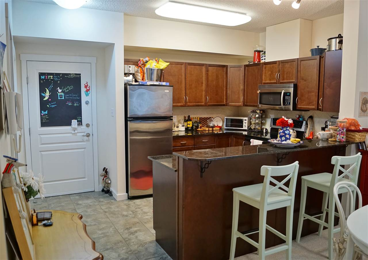 2) Dark maple cabinetry, granite countertops, stainless steel appliances