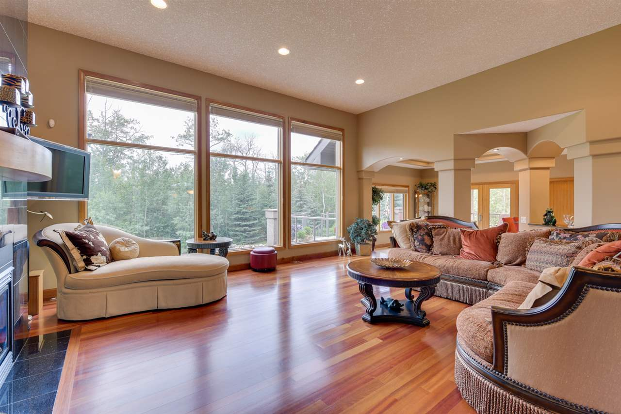 Floor to ceiling panoramic windows, Granite wall with gas fireplace and cherry hardwood flooring in this family room