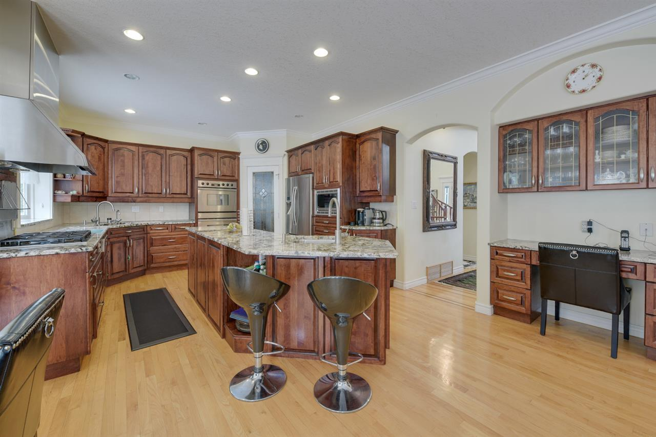 gourmet kitchen with cherry cabinets, gigantic island, walk through pantry and a telephone/computer desk
