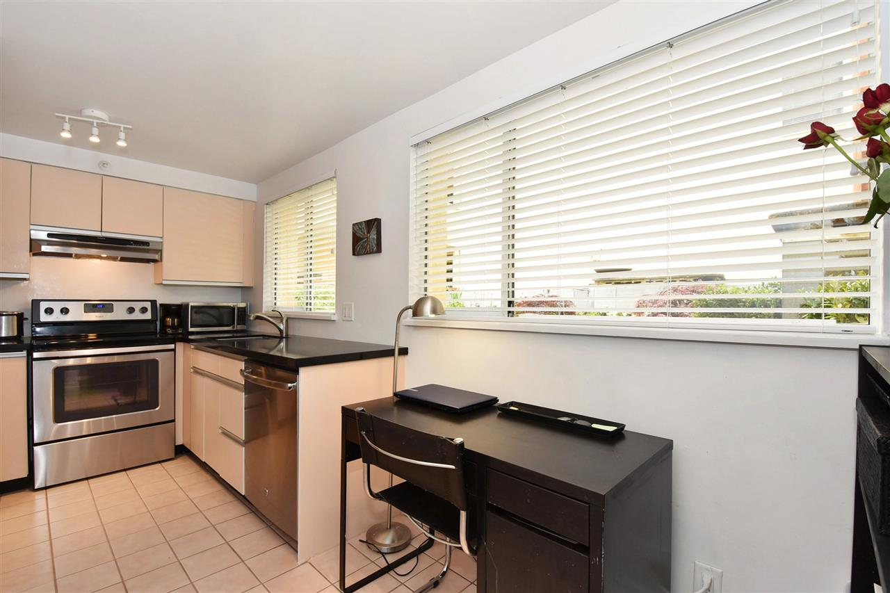 Light filled kitchen with large windows and area for desk or additional seating.