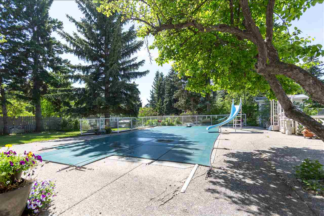 Beautiful South West, fully landscaped yard with very well maintained saline in-ground swimming pool, many mature trees, a lovely patio and built in BBQ area, on a 12,241 sq ft Lot with back ally.