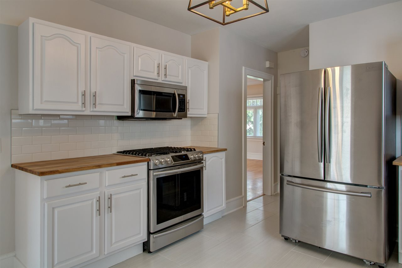 Gas range, new s/s appliances, solid wood counters, subway tile backsplash and new ceramic tile