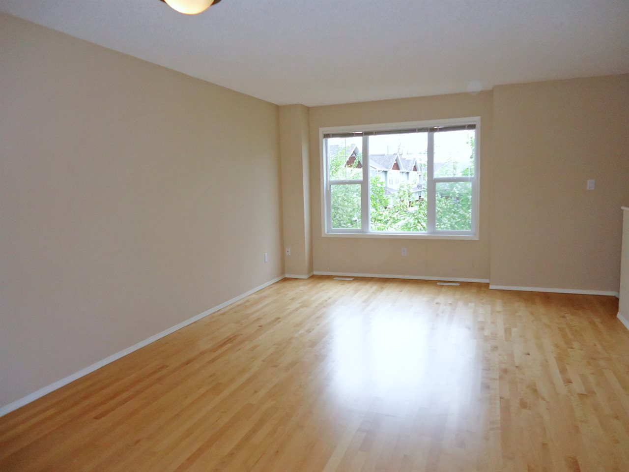 Large open living/dining area with refinished modern looking hardwood floors.