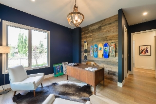 Den on main floor has a custom rustic wood feature wall and a large walk-in closet with custom built-in cabinetry.