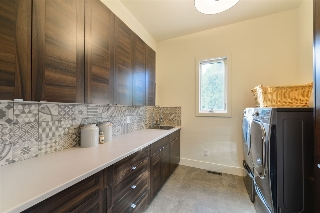 Main floor laundry room with custom backsplash and top of the line washer/dryer.