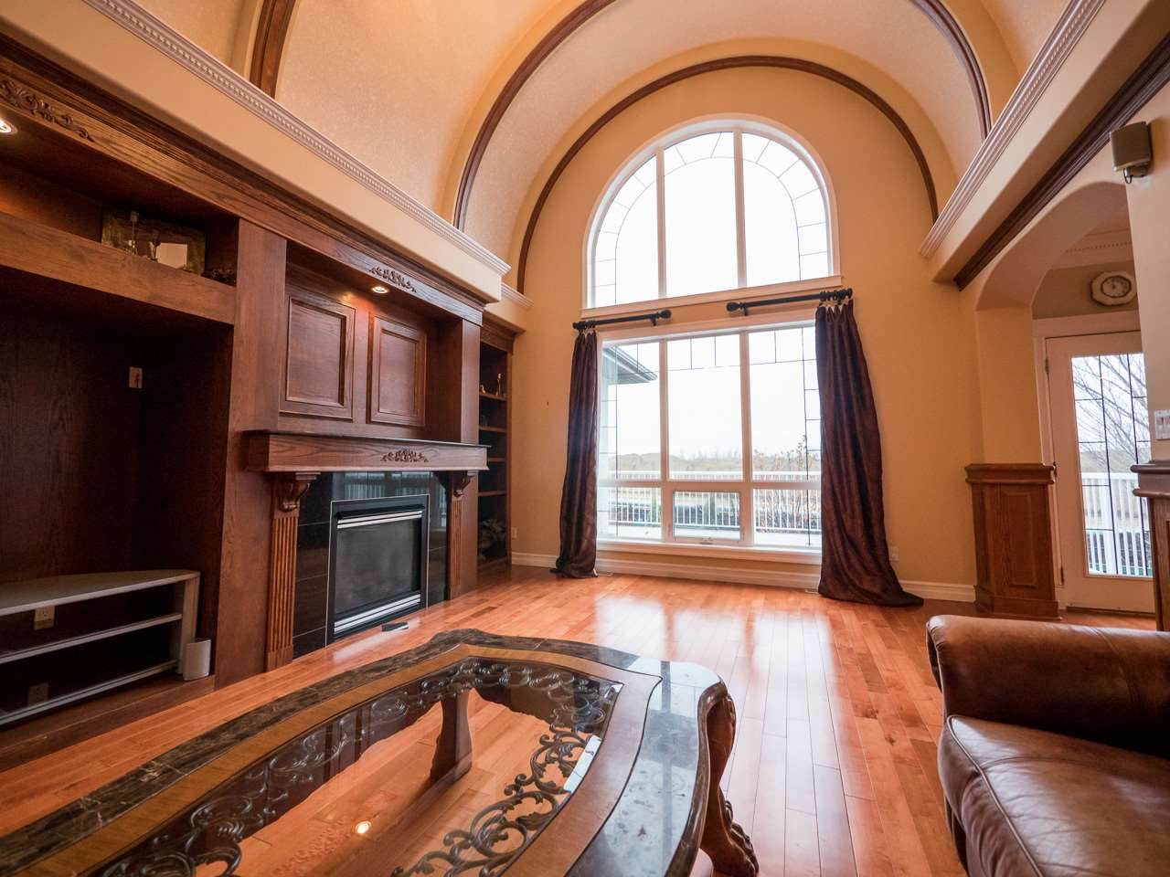 Stunning Great Room with arched rib ceiling, large windows allowing lots of natural light to shine through, and a built-in wall unit with fireplace.