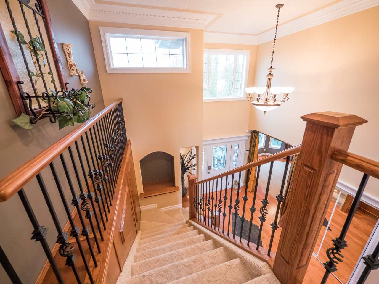 Staircase leading from the grand foyer to the upper level loft.