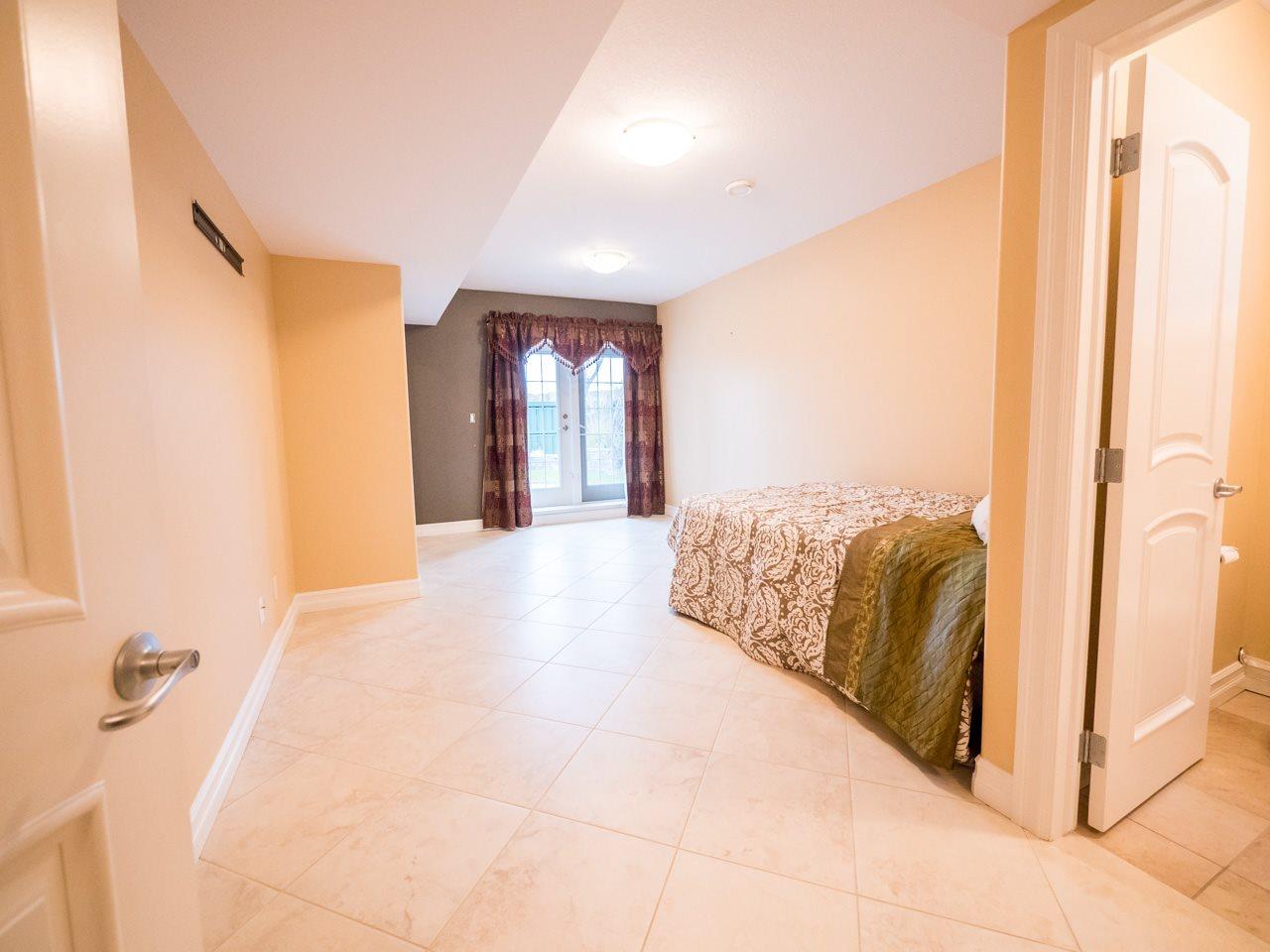 Second lower level bedroom features its own en suite bath.  Patio doors from the bedroom lead to the a large patio.