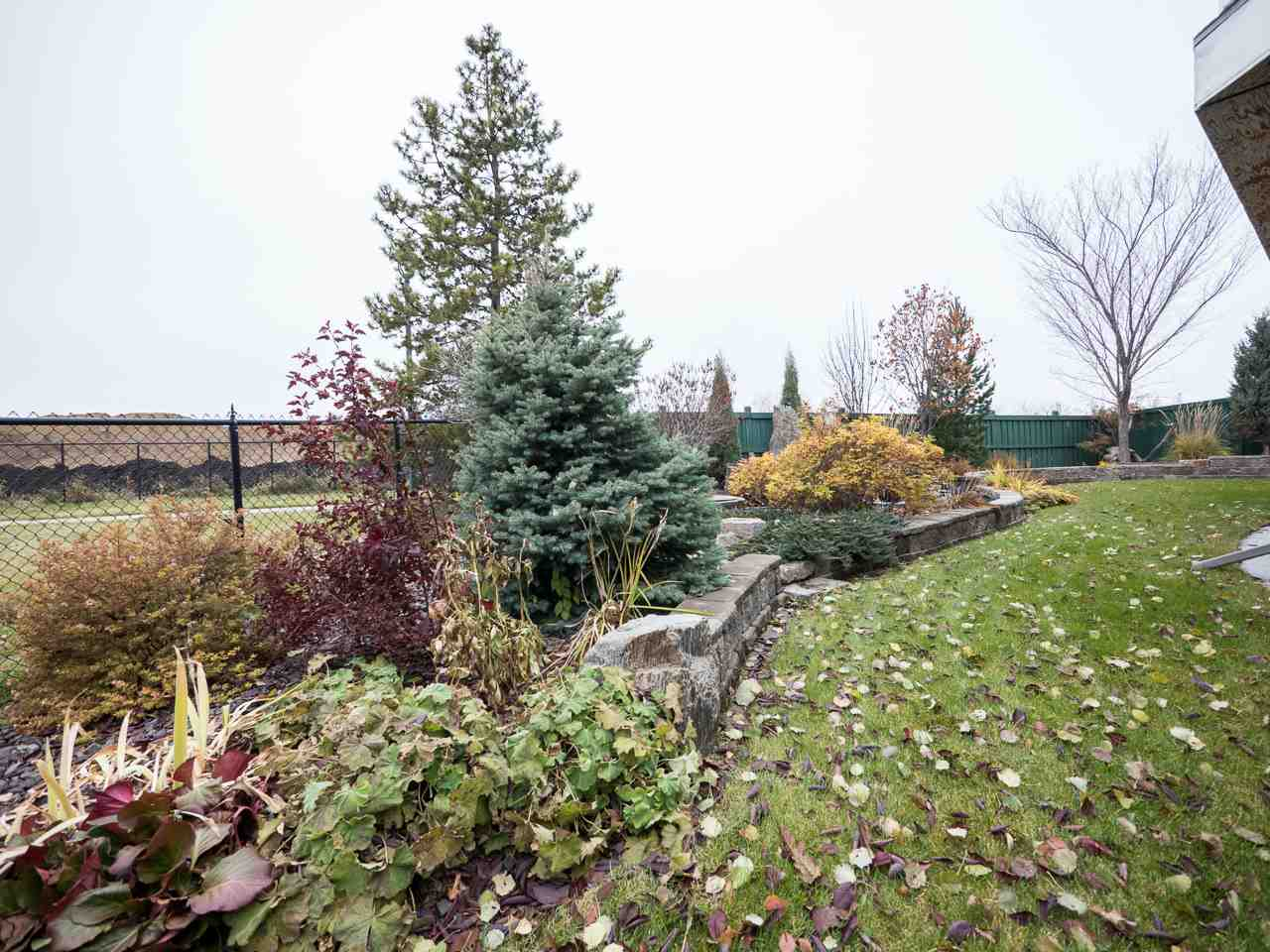 Professionally landscaped and yard boasts mature trees, shrubs and perennials, and terraced steps. Pie lot backs a park, greenspace and walking trail.