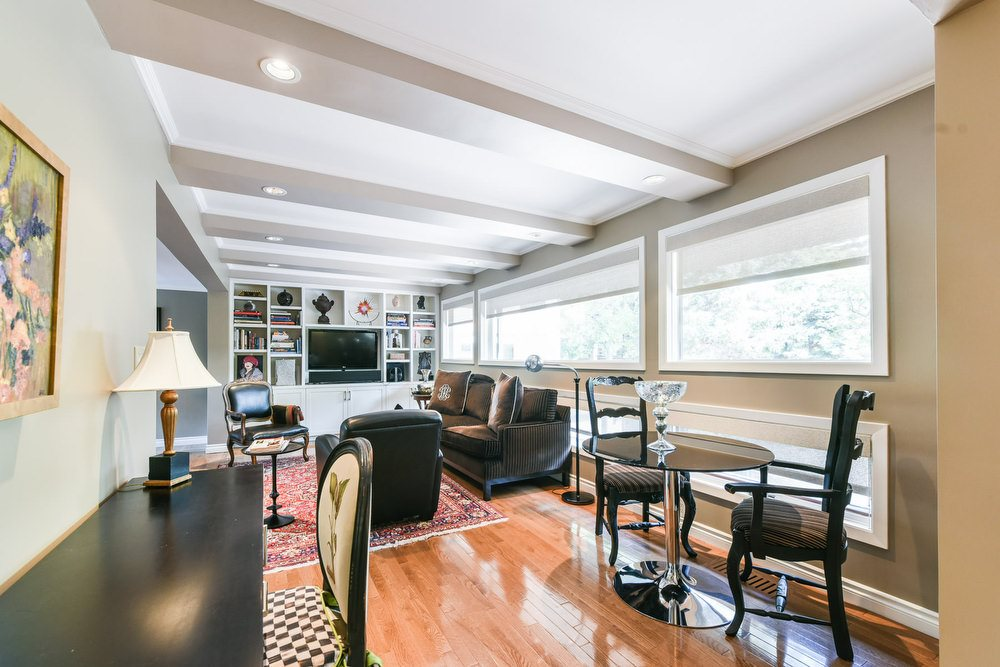 The family room is open to the breakfast nook with floor-to-ceiling and wall-to-wall windows to allow an abundance of  natural light to enter the home.