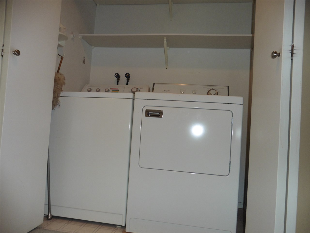 Convenient in-suite laundry closet with overhead shelving.
