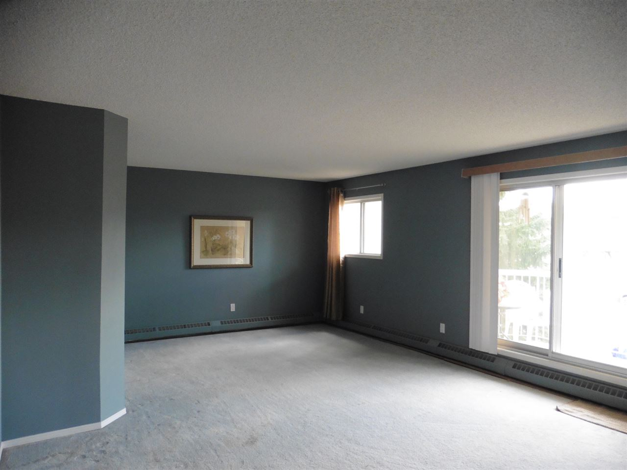 Spacious and bright living room area with patio doors opening to balcony.