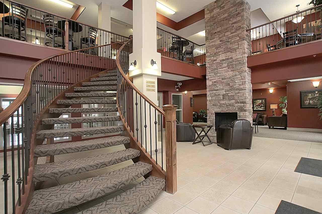 You are welcomed from the front door into a large two storey foyer where you will find this sweeping stairwell leading to a games area. The main floor entrance has a view of the salt water pool, two storey stone fireplace and comfortable seating.