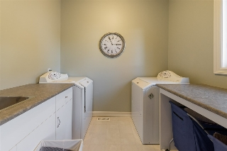 Separate laundry room features a sink and sorting/wrapping centre..