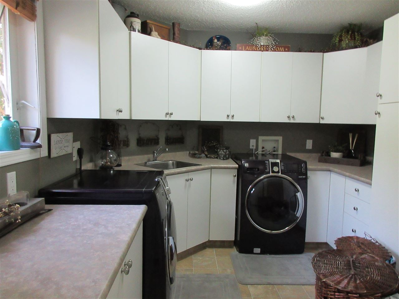 This main floor laundry has lots of cabinets at one end and room for a freezer at the other end