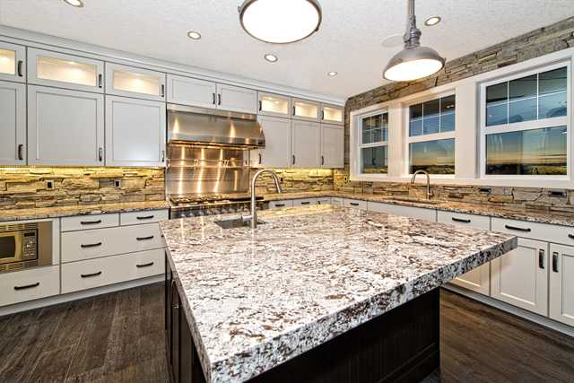 Loads of cabinets with upper cabinets having glass accent doors along with two stainless steel sinks (prep sink in island) and extensive use of stone throughout the back splash.