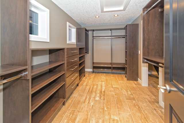 Huge walk in closet with loads of custom built-in cabinets.