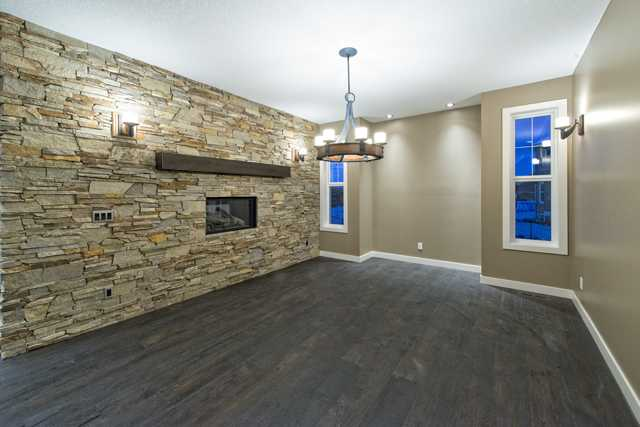 Two sided gas fireplace trimmed by a stone wall with mantle also having custom upgraded lighting and cantilever for a hutch.