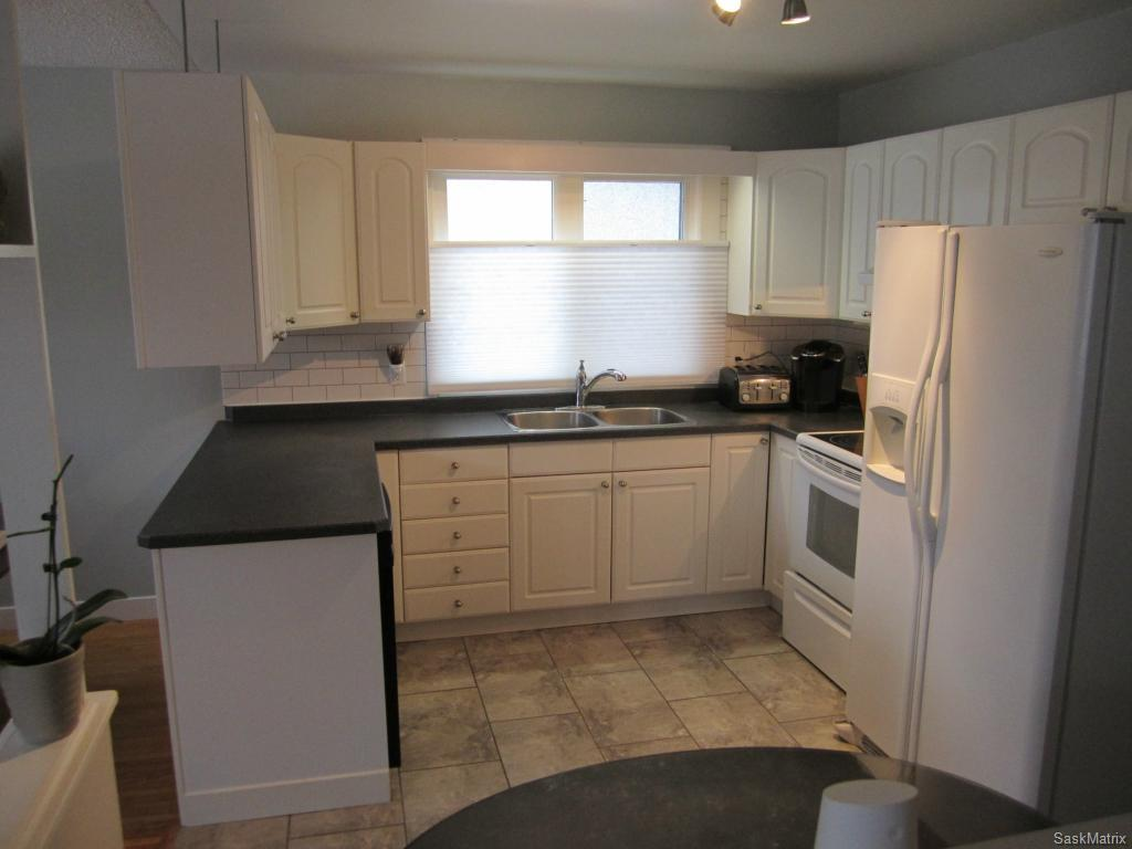 Newer white kitchen cabinets and ceramic tile flooring.