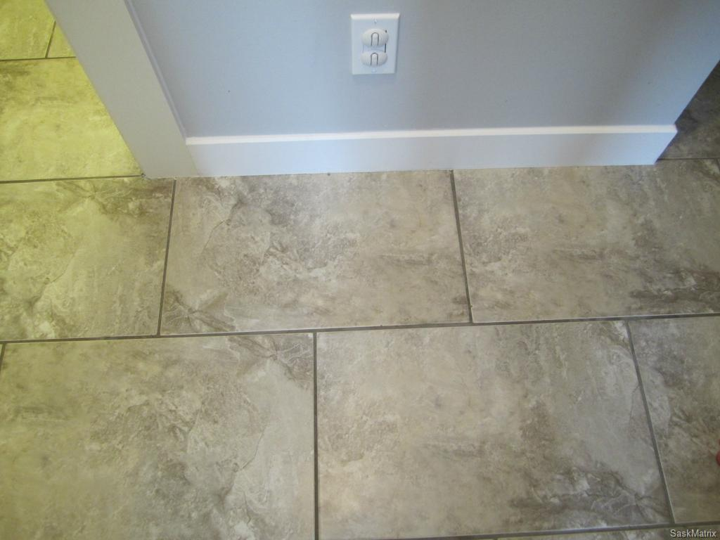 Contemporary ceramic tile in kitchen, bathroom, and hallways. New baseboards & trims throughout the main level.