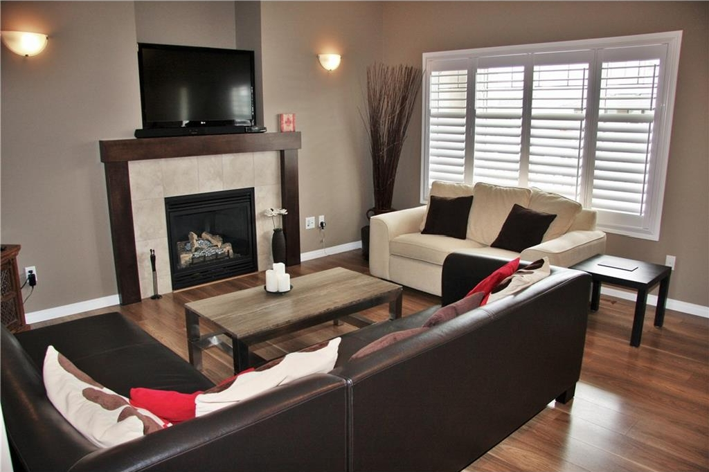 Spacious living room with laminate floor, check out that beautiful fireplace and the plantation shutters!