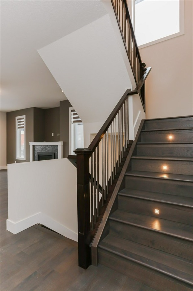 Staircase has hardwood and built in lighting