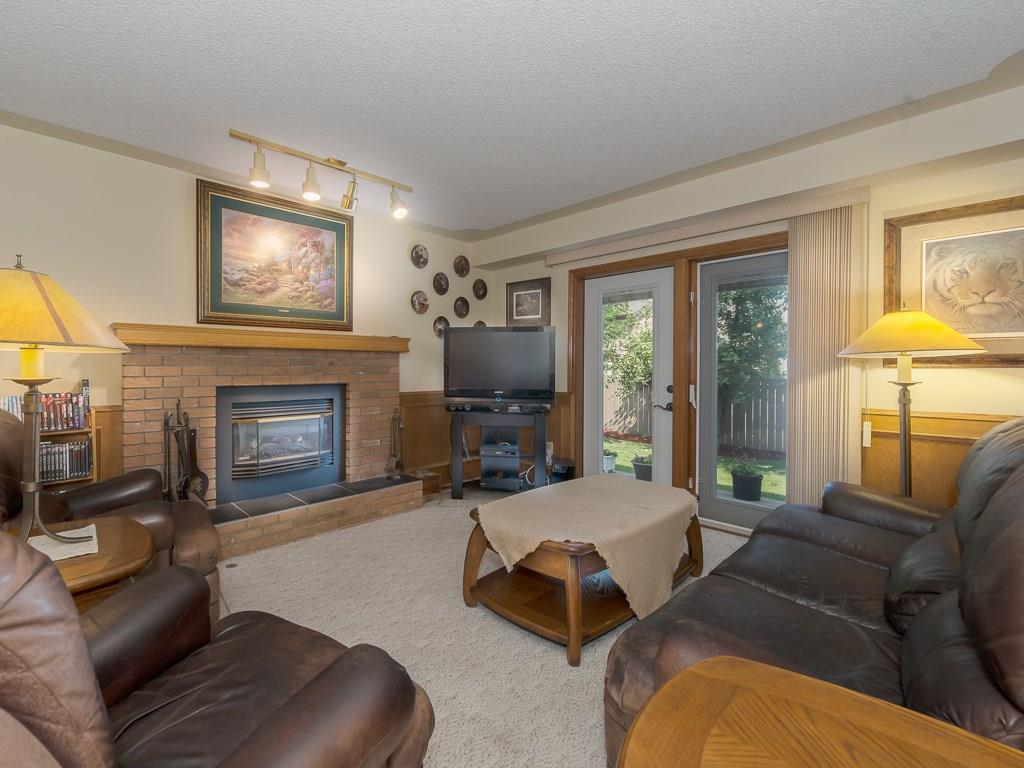 Family room with brick trimmed gas fireplace and patio doors leading to the backyard.