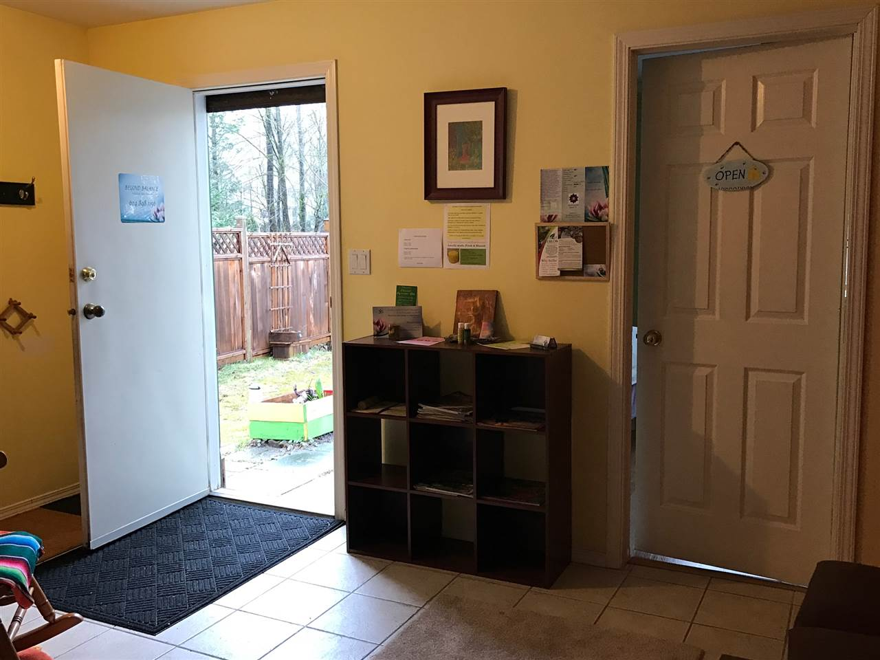 "Downstairs ""flex"" utility space - entry from rear yard with 2 bedrooms bath and recreation room adjacent. Closed door on the right is ""healing room"" no photos at tenants request . Is one of 2 bedrooms on lower level."
