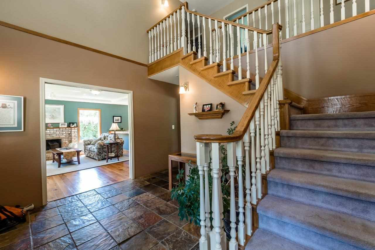 Slate tile entry with open stairway to upper level...  Access to Living room Kitchen & stairs down to basement. 2 step convenience to home office /den.