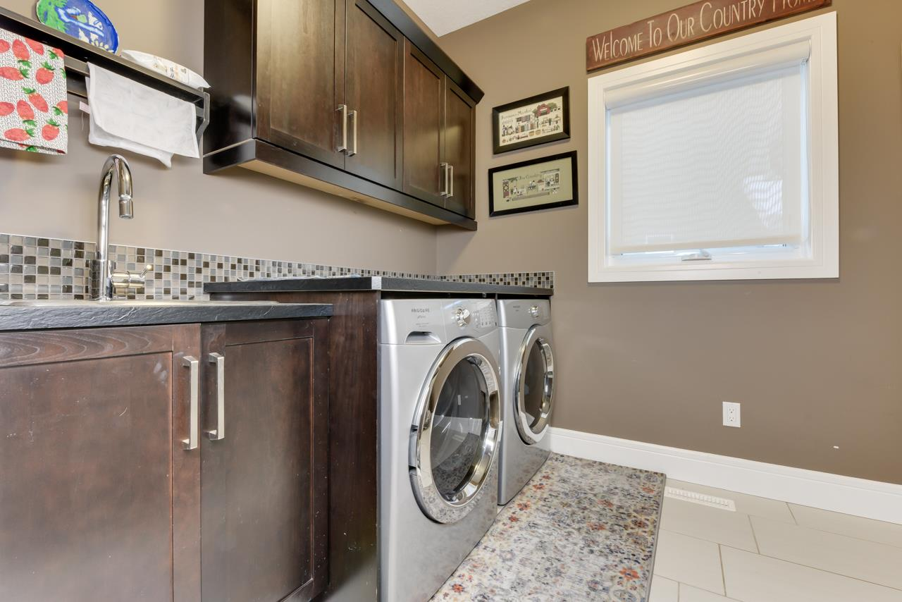 Spacious Main Floor laundry with Front Load Washer & Dryer, Sink and Cabinetry separated from the boot room