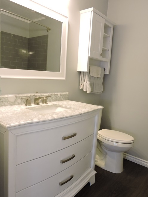 Main floor bathroom with amazing new vanity, toilet, subway tile, faucets and vinyl plank flooring.