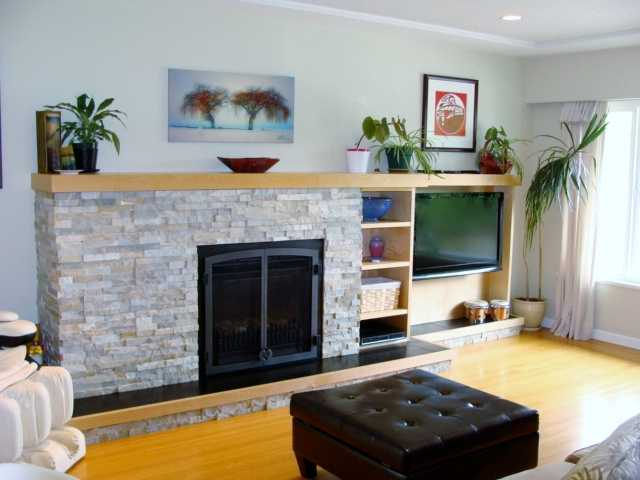 Living room has gas fireplace accented with ledgestone