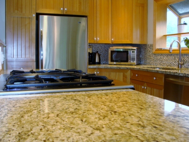 Thick granite countertops with tile backsplash and cabinets to ceiling