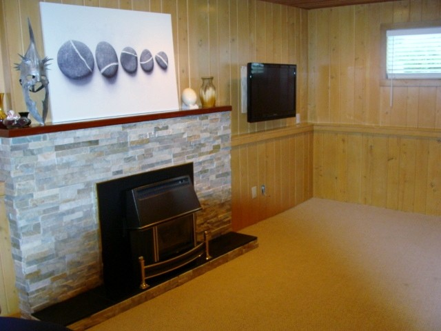 Below family room with ledgestone work around gas fireplace