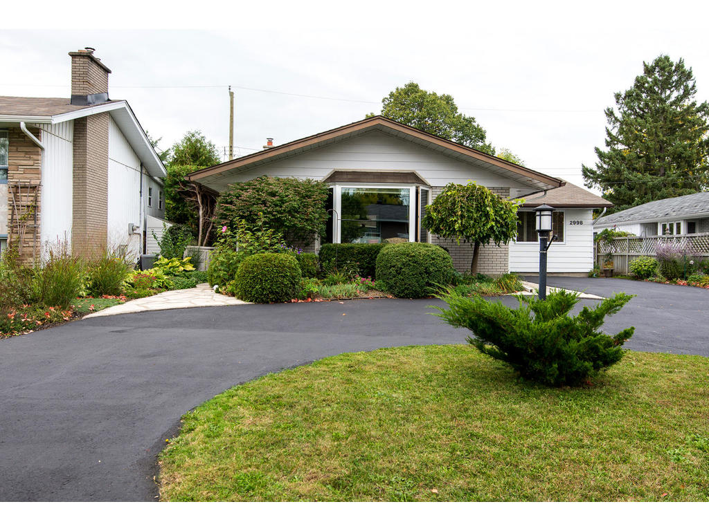 2998 Linton Road, beautifully landscaped with circular driveway.