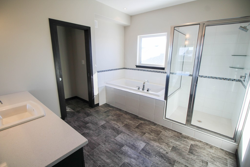 Spacious ensuite bathroom with soaker tub and shower stall