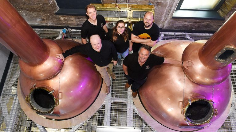 aerial view holyrood distillery staff next to stills